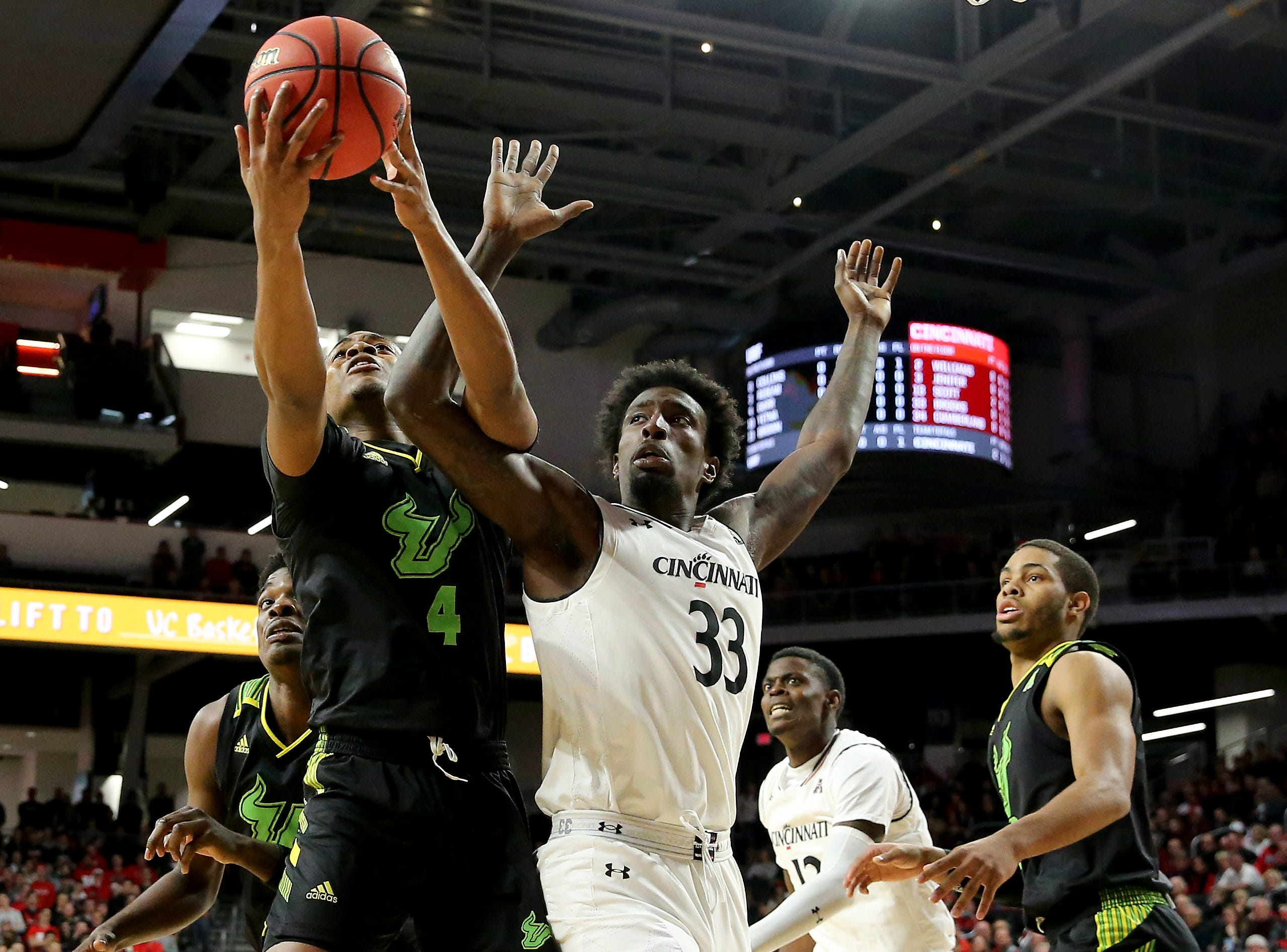 South Florida Bulls forward Michael Durr (4) and Cincinnati Bearcats center Nysier Brooks (33) battle for a rebound in the first half of an NCAA college basketball game, Tuesday, Jan. 15, 2019, at Fifth Third Arena in Cincinnati.