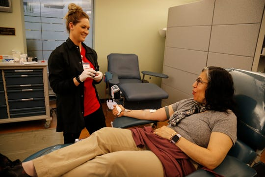 Phlebotomist Calee Downs collects a donation from Enquirer reporter Anne Saker at the Hoxworth Blood Center in the Corryville neighborhood of Cincinnati on Wednesday, Jan. 16, 2019.