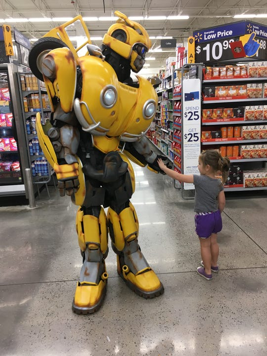 The Bumblebee Transformer character greets a girl at an Arkansas Walmart.