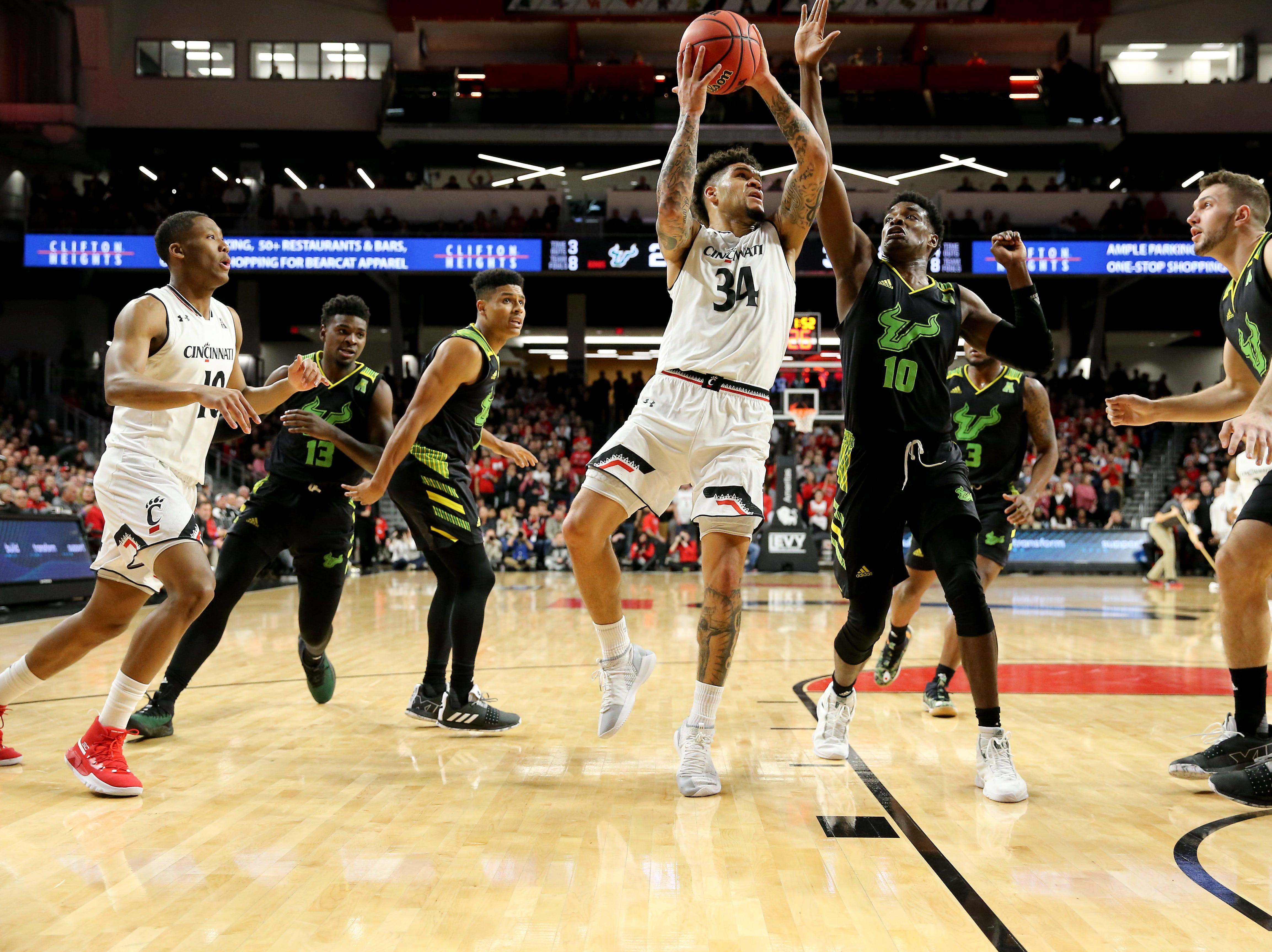 Cincinnati Bearcats guard Jarron Cumberland (34) goes up for a shot as South Florida Bulls forward Alexis Yetna (10) defends in the first half of an NCAA college basketball game, Tuesday, Jan. 15, 2019, at Fifth Third Arena in Cincinnati.