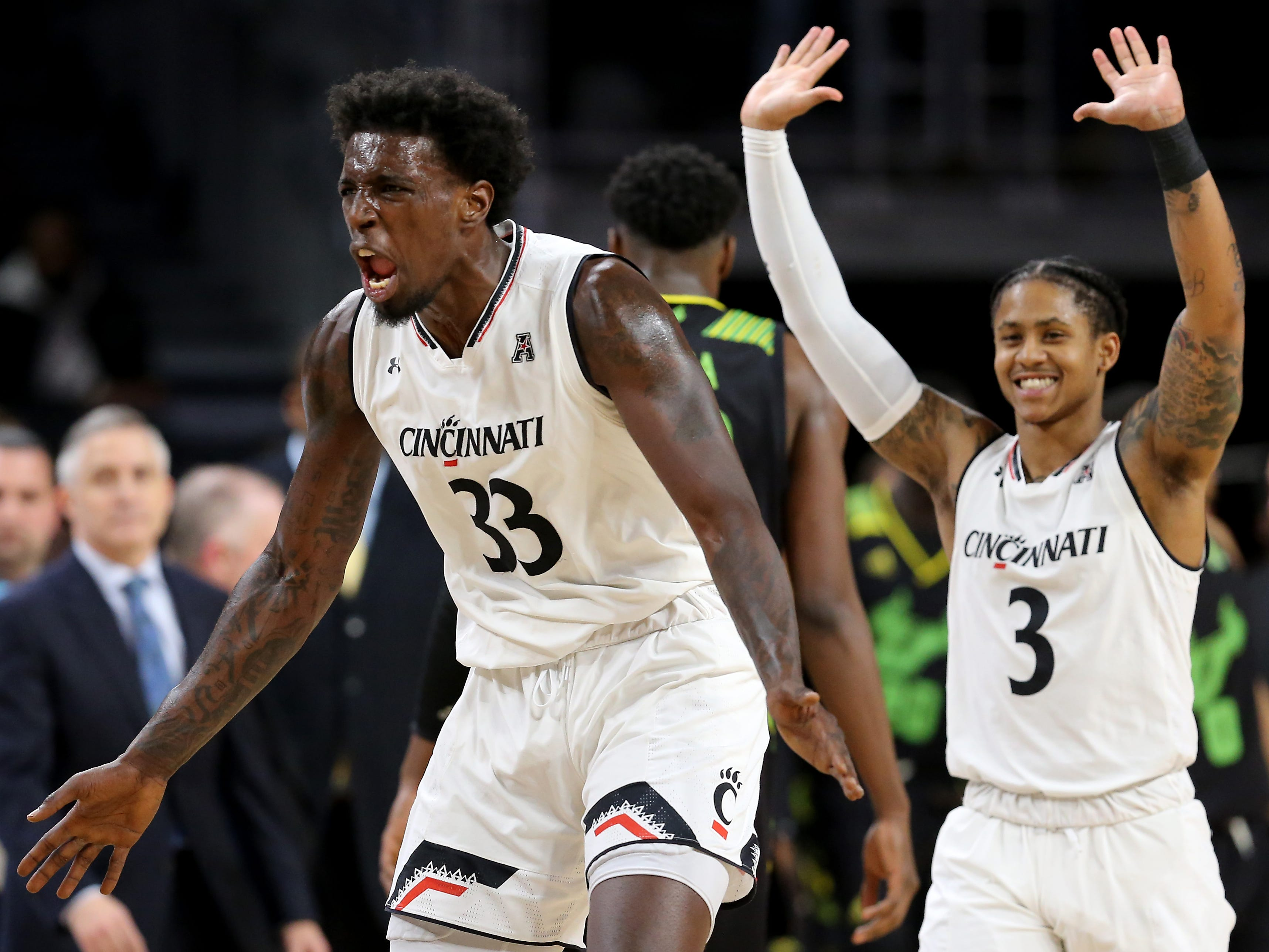 Cincinnati Bearcats center Nysier Brooks (33) and Cincinnati Bearcats guard Justin Jenifer (3) celebrate a lead after a timeout is called in the second half of an NCAA college basketball game against the South Florida Bulls, Tuesday, Jan. 15, 2019, at Fifth Third Arena in Cincinnati. Cincinnati won 82-74.