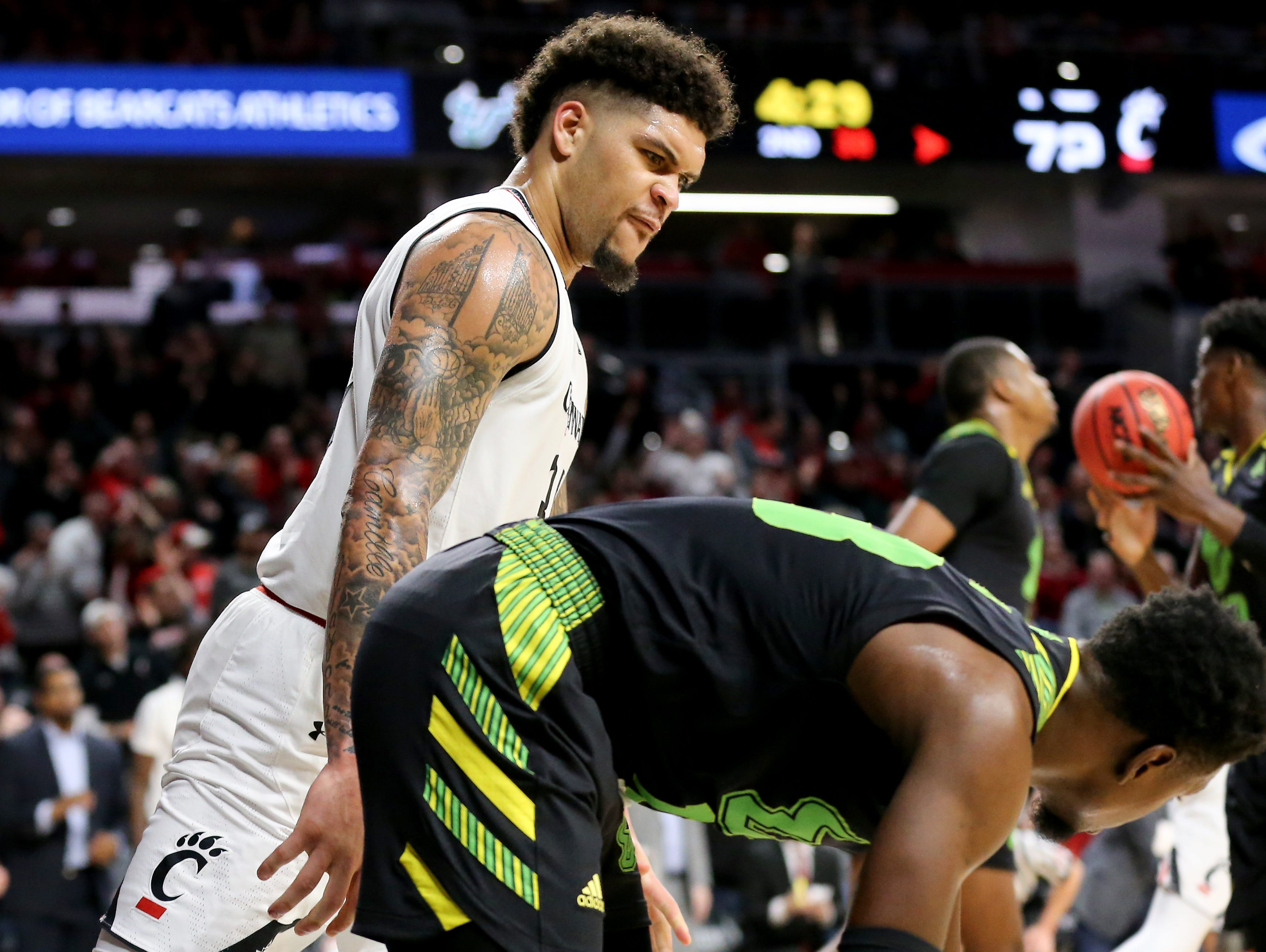 Cincinnati Bearcats guard Jarron Cumberland (34) stares down South Florida Bulls guard Justin Brown (13) in the second half of an NCAA college basketball game, Tuesday, Jan. 15, 2019, at Fifth Third Arena in Cincinnati. Cincinnati won 82-74.