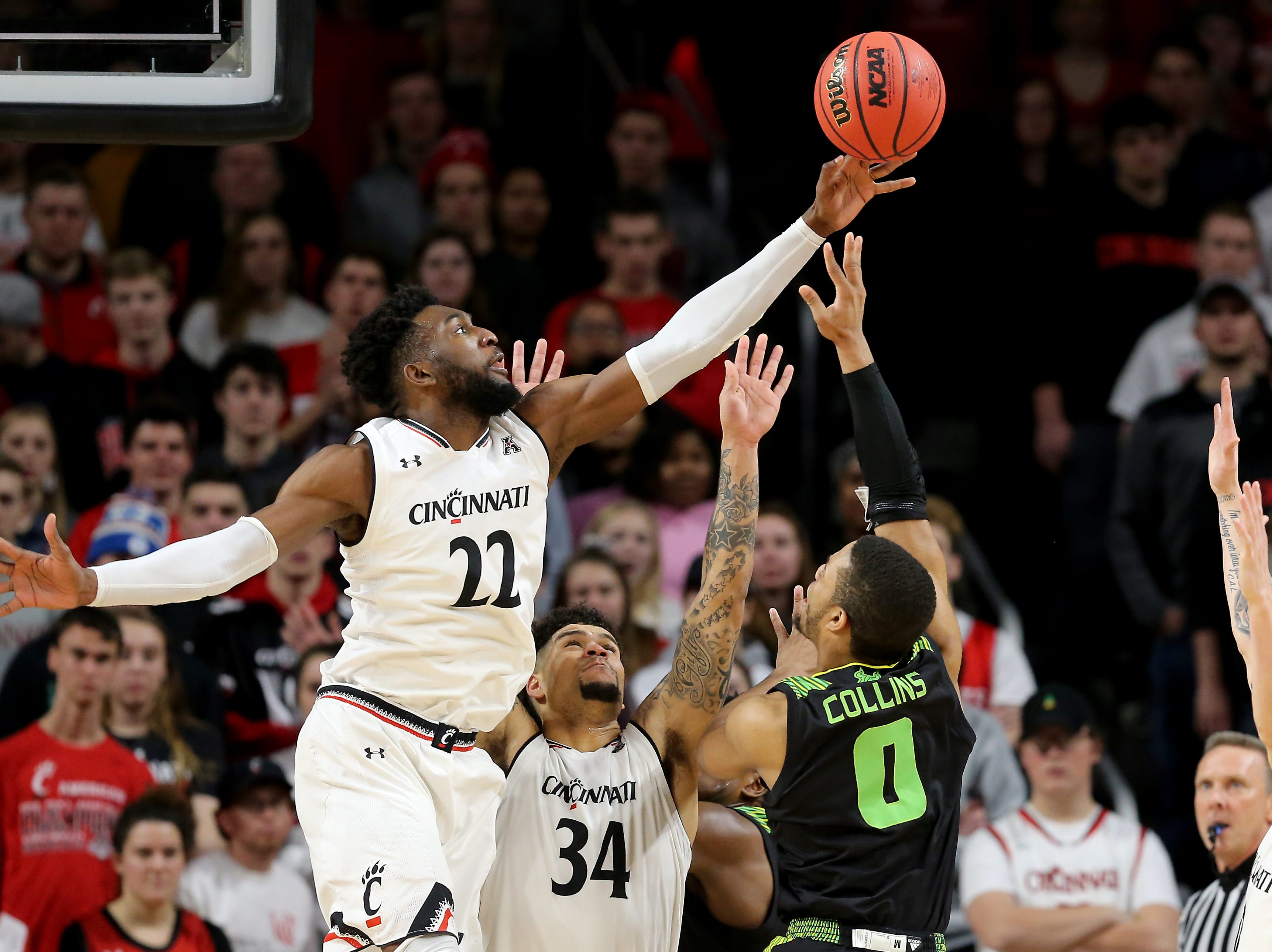 Cincinnati Bearcats forward Eliel Nsoseme (22) blocks South Florida Bulls guard David Collins' (0) shot in the first half of an NCAA college basketball game, Tuesday, Jan. 15, 2019, at Fifth Third Arena in Cincinnati.