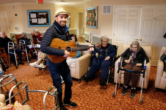 Ryan Brolliar plays his guitar among Chelsea residents