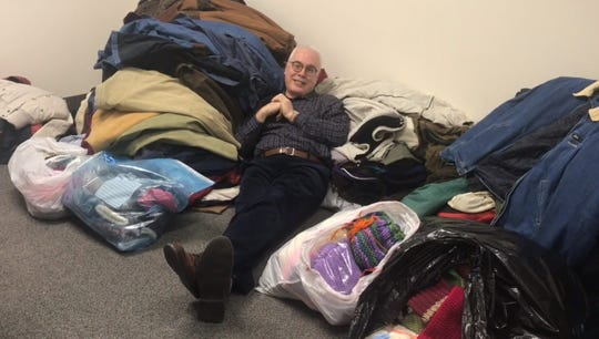 Paul C. Grzella sitting with a pile of coats  collected during a coat drive by the Courier News, Home News Tribune and My Central Jersey.