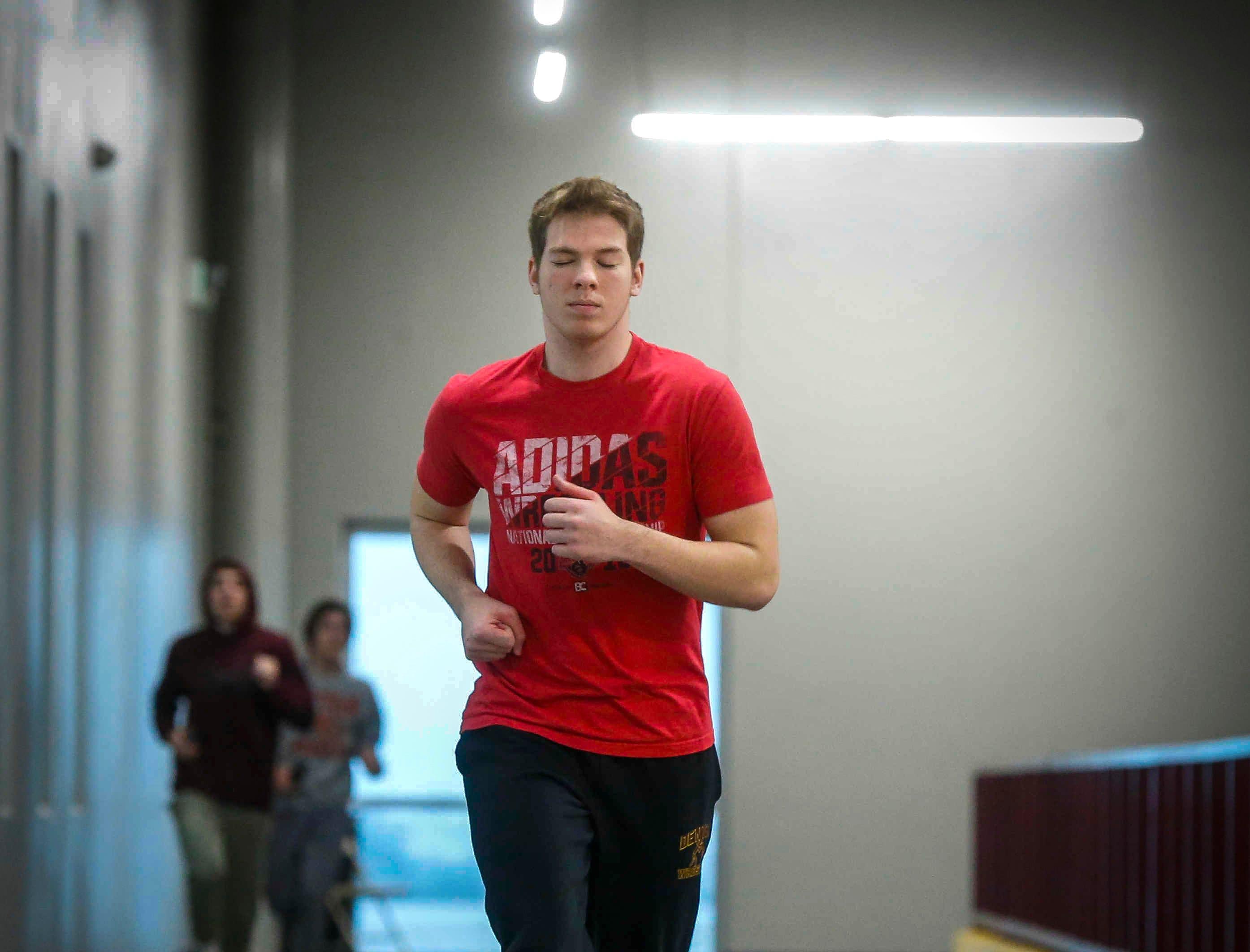 Denver sophomore wrestler Cam Krueger runs laps prior to wrestling practice at the Denver High School in Denver on Tuesday, Jan. 15, 2019. Krueger was born legally blind.
