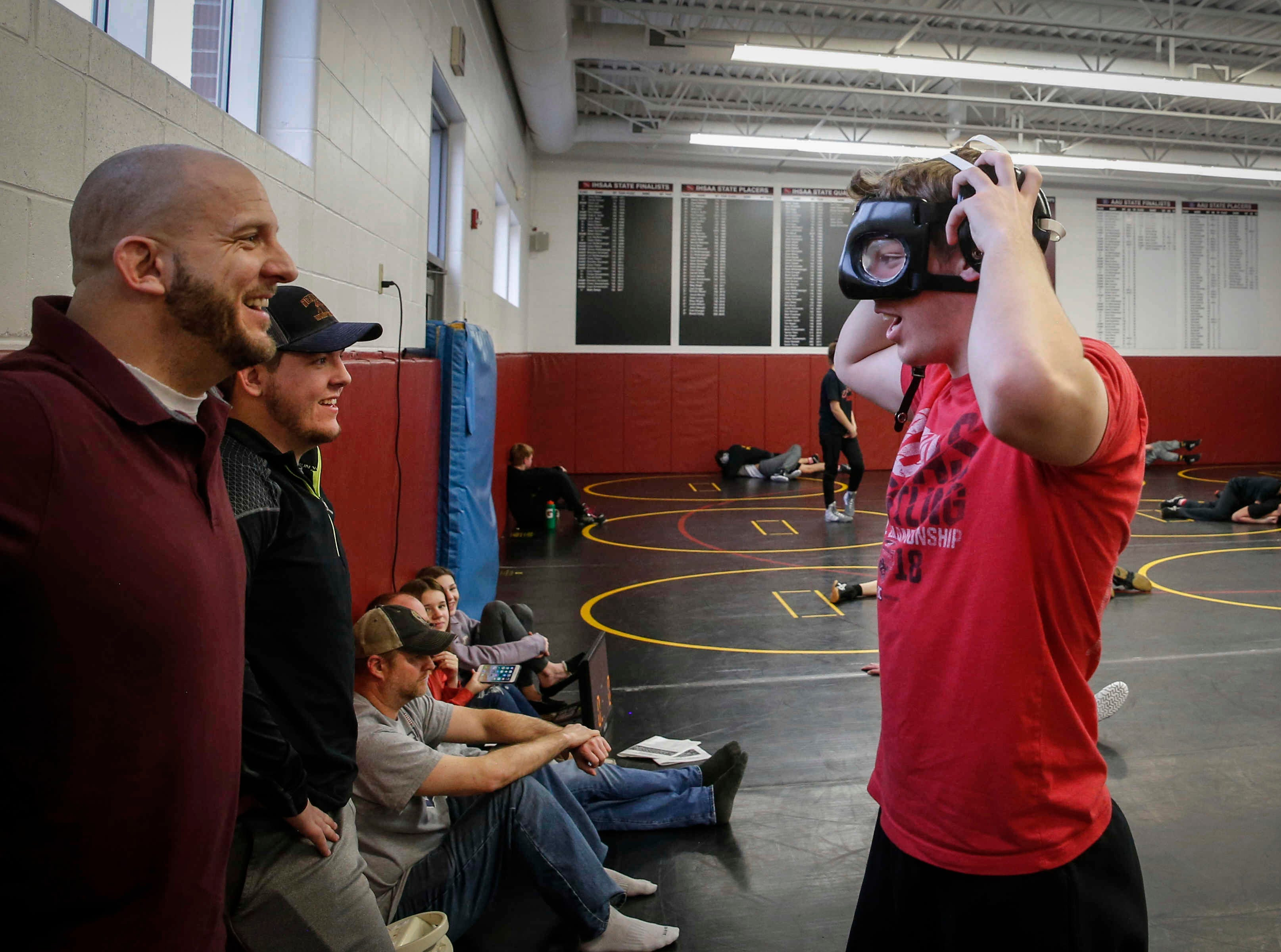 Denver sophomore Cam Krueger, right, jokes with his father, head wrestling coach Chris Krueger, and brother Cael, prior to running drills during wrestling practice at Denver High School in Denver on Tuesday, Jan. 15, 2019. Krueger hasn't let the fact that he is legally blind step in the way of his passion for wrestling.