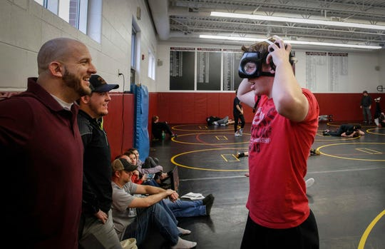 Denver sophomore Cam Krueger, right, jokes with his father, head wrestling coach Chris Krueger, and brother Creed, prior to running drills during wrestling practice at Denver High School in Denver on Tuesday, Jan. 15, 2019. Krueger hasn't let the fact that he is legally blind step in the way of his passion for wrestling.