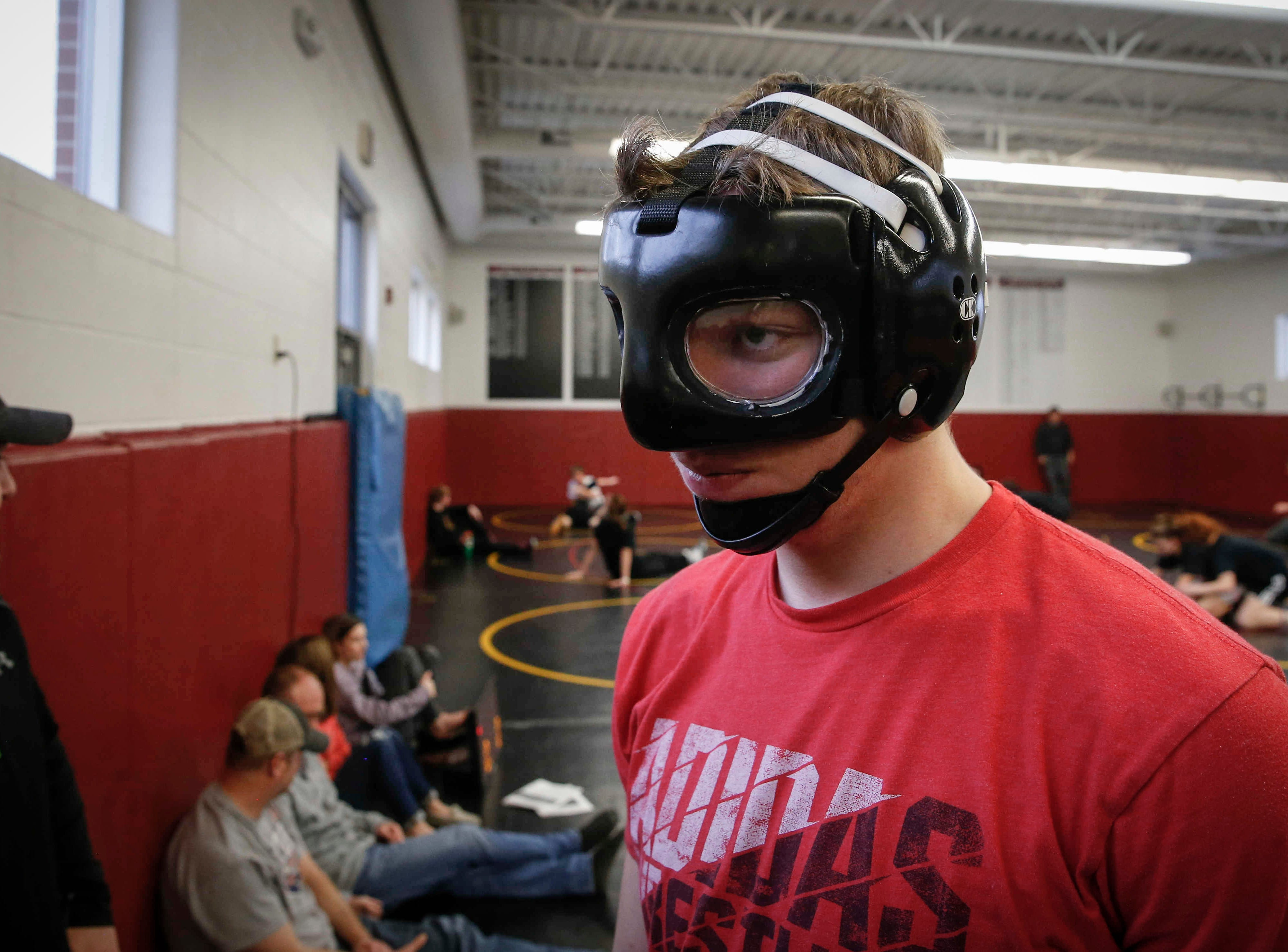Denver sophomore Cam Krueger wears a protective mask before running drills during wrestling practice at Denver High School in Denver on Tuesday, Jan. 15, 2019. Krueger hasn't let the fact that he is legally blind step in the way of his passion for wrestling.