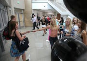 Ankeny Centennial senior Maddie Decker hands out school pens to arriving students during the first day of school in 2013.