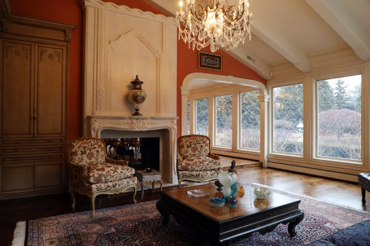 A sunroom with grand piano and chandelier shares an elaborate fireplace with the formal dining room.