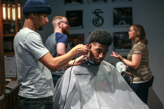 Lonell Carr, 28, of Oak Park, left cuts Willie Garwood's, 23, of Detroit, hair at the Social Club Grooming Company on \ Wayne State University's campus in Detroit on Friday, Jan. 11, 2019. Sebastian Jackson, co-owner, says he wanted to preserve the safe space for dialogue known in a black barbershop, but also have different races of barbers to expand the dialogue.
