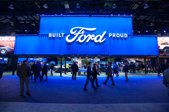 People check out the vehicles and other attractions in the Ford Motor Company exhibit space at the North American International Auto Show at Cobo Center. The company said Wednesday that profit-sharing checks would go out March 14. The amount is based on North American earnings, which was $7.6 billion before interest and taxes in 2018.