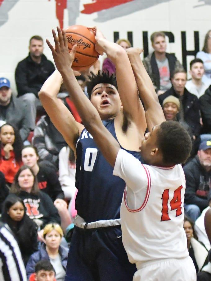 Roseville's John Ukomadu (14) defends a shot by Dakota's Xavier Glenn (10) in the first quarter as Roseville hosts Dakota at Roseville High School, Tuesday night,  January 15, 2019.