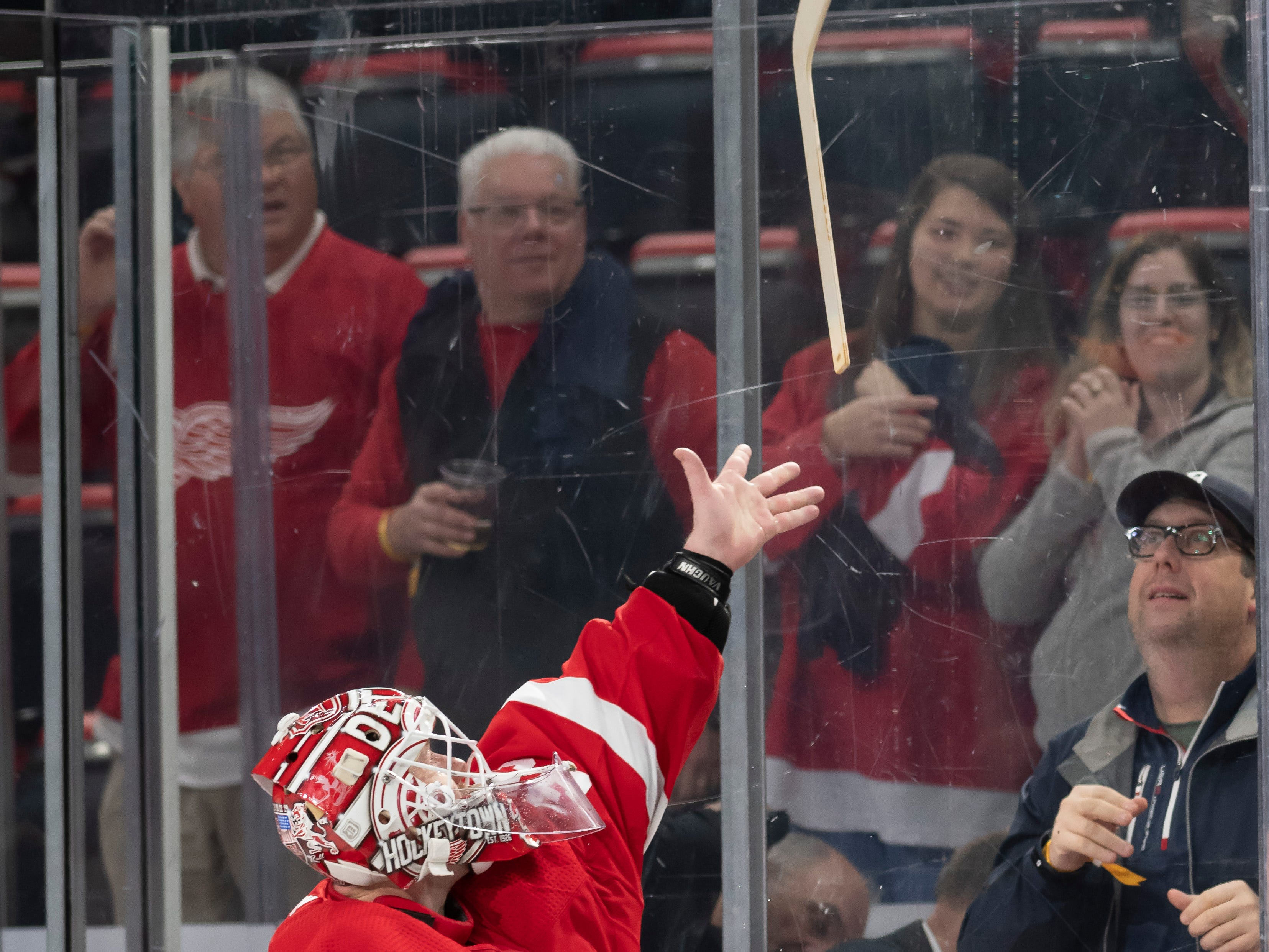 Detroit goaltender Jimmy Howard throws a stick to a fan after the game.