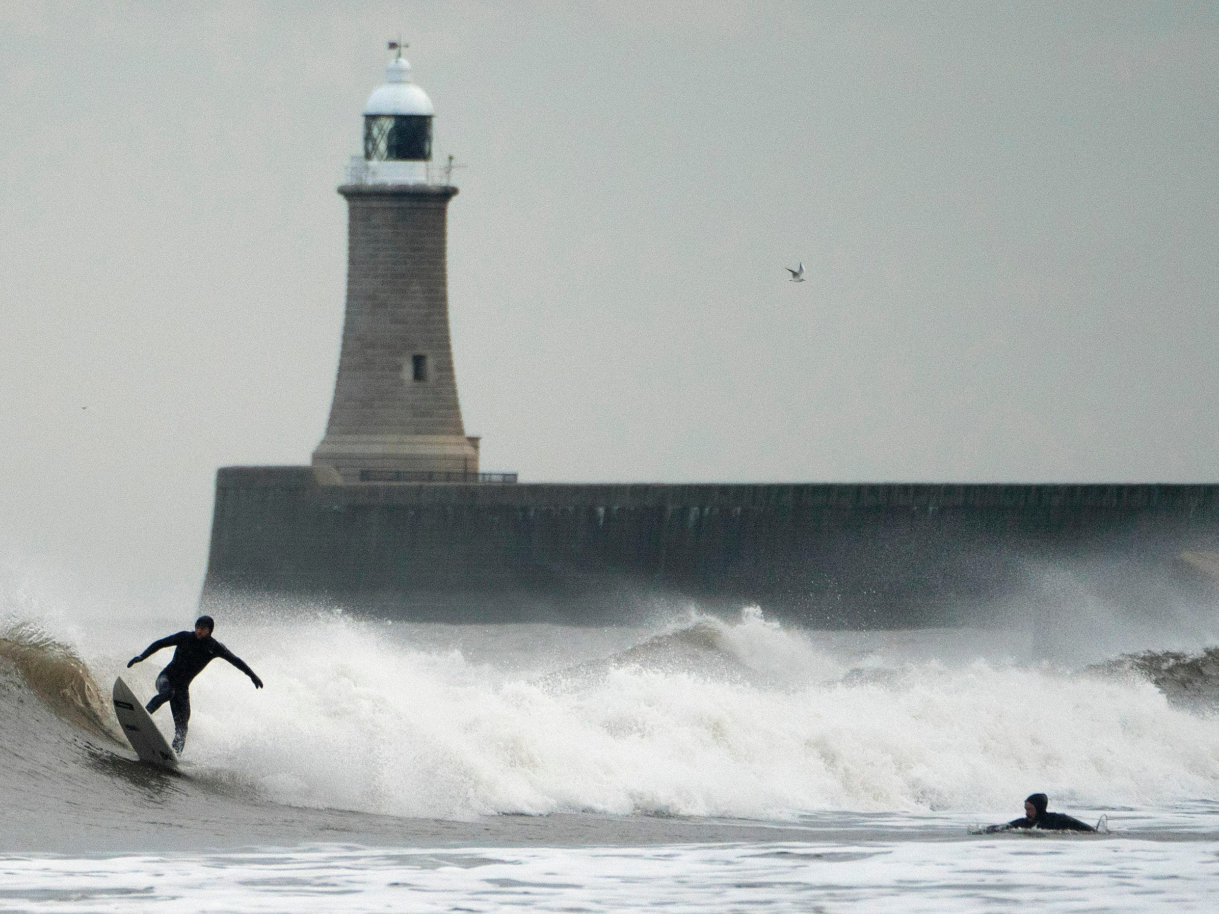 Surfers on Wednesday Jan. 16, 2019 take on the waves at Tynemouth in northeast England, where the weather is predicted to get much colder in the coming days. Britain's Met Office has issued a warning for snow and ice over parts of Scotland and northern England.