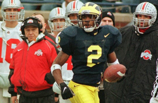 The Ohio State bench looks on as Michigan's Charles Woodson, right, returns a 78-yard punt return for a touchdown during the second quarter at Michigan Stadium in Ann Arbor on Nov. 22, 1997.