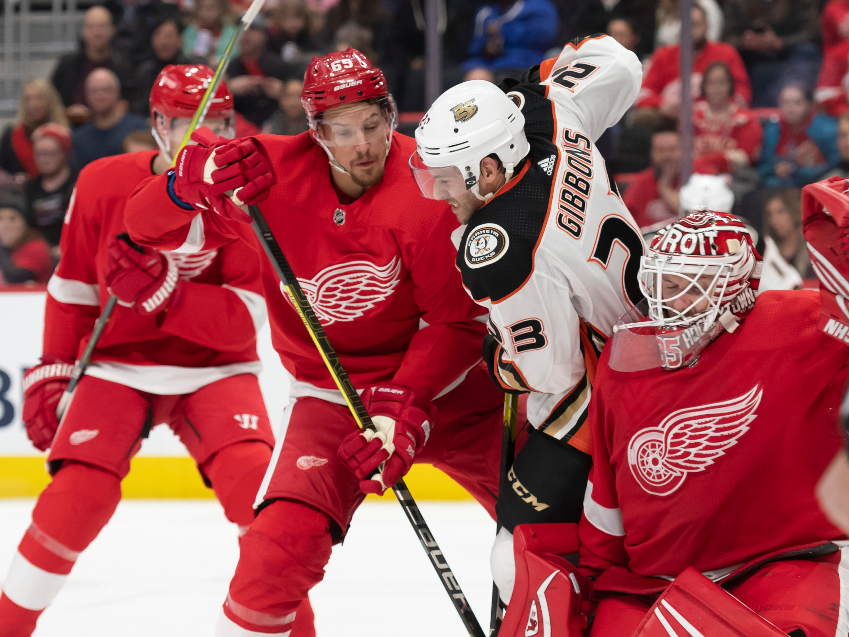 Detroit defenseman Danny DeKeyser, left, and goaltender Jimmy Howard battle for the puck with Anaheim center Brian Gibbons in the second period.