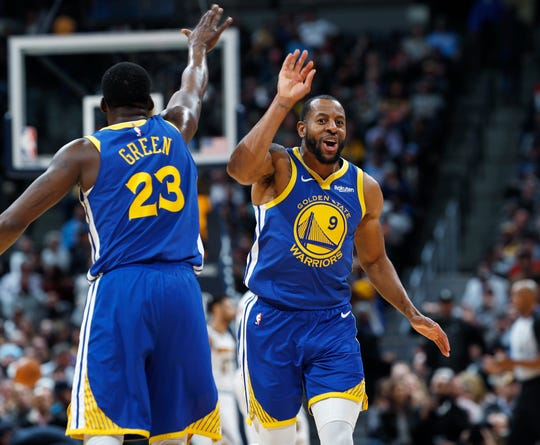 Golden State Warriors forward Draymond Green, left, congratulates guard Andre Iguodala after his dunk against the Denver Nuggets on Tuesday.
