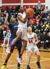 Roseville's Darien Banks (5) goes to the basket in front of Dakota's Joshua Hines, left, in the second quarter. Banks finished with 16 points, including three 3-pointers, in Roseville's 63-56 victory.