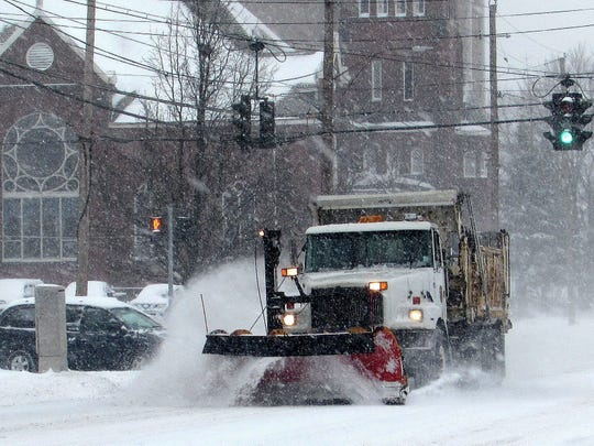 A plow clears snow from Madison Avenue in Elmira during a past snowstorm. Officials are gearing up for another storm this weekend.