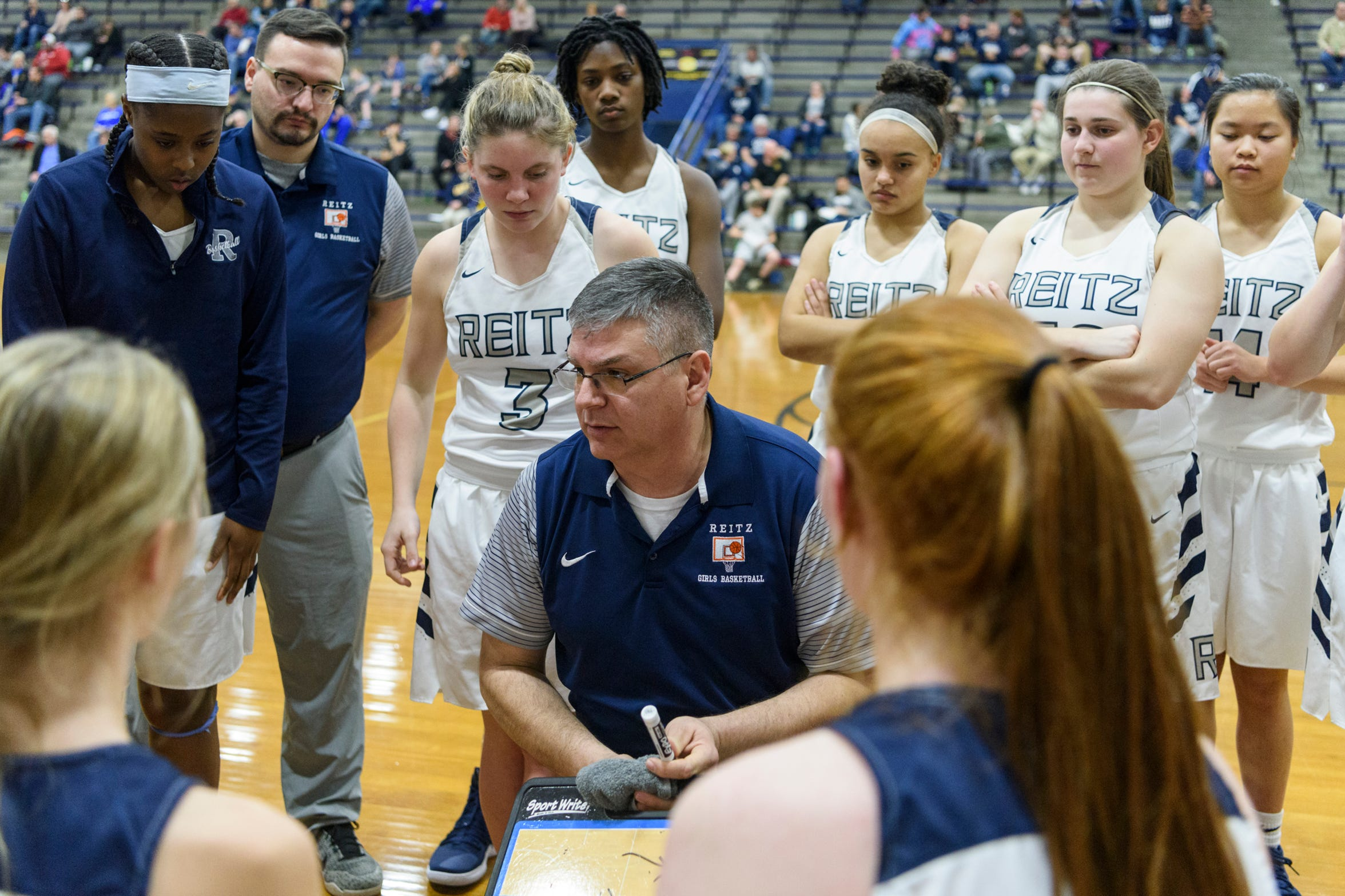 Reitz Head Coach Gary Loveless, center, strategizes with his team as they take on the Castle Knights at F.J. Reitz High School in Evansville, Ind., Thursday, Jan. 3, 2019. The Panthers were defeated by the Knights, 51-17.