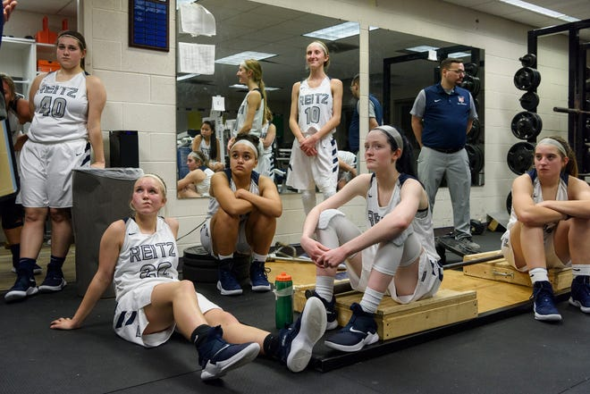The Reitz Lady Panthers listen to Head Coach Gary Loveless, not pictured, in the locker room during halftime against the Castle Knights at F.J. Reitz High School in Evansville, Ind., Thursday, Jan. 3, 2019. The Panthers were defeated by the Knights, 51-17.