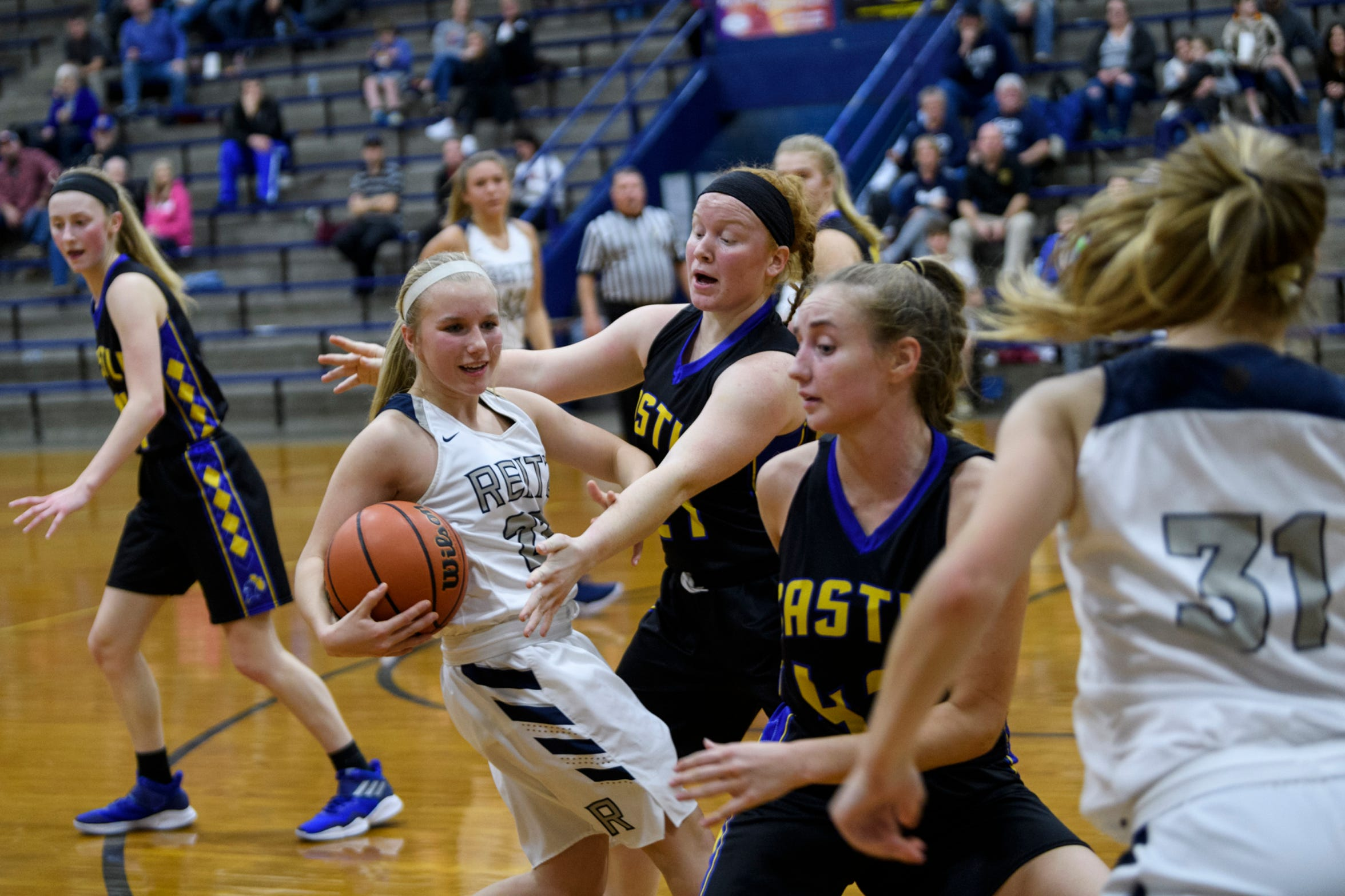 Reitz's Alyssa Haynes (22) keeps the ball away from Castle defender Kial Mitchell (21) during the game at F.J. Reitz High School in Evansville, Ind., Thursday, Jan. 3, 2019. The Knights defeated the Panthers, 51-17.