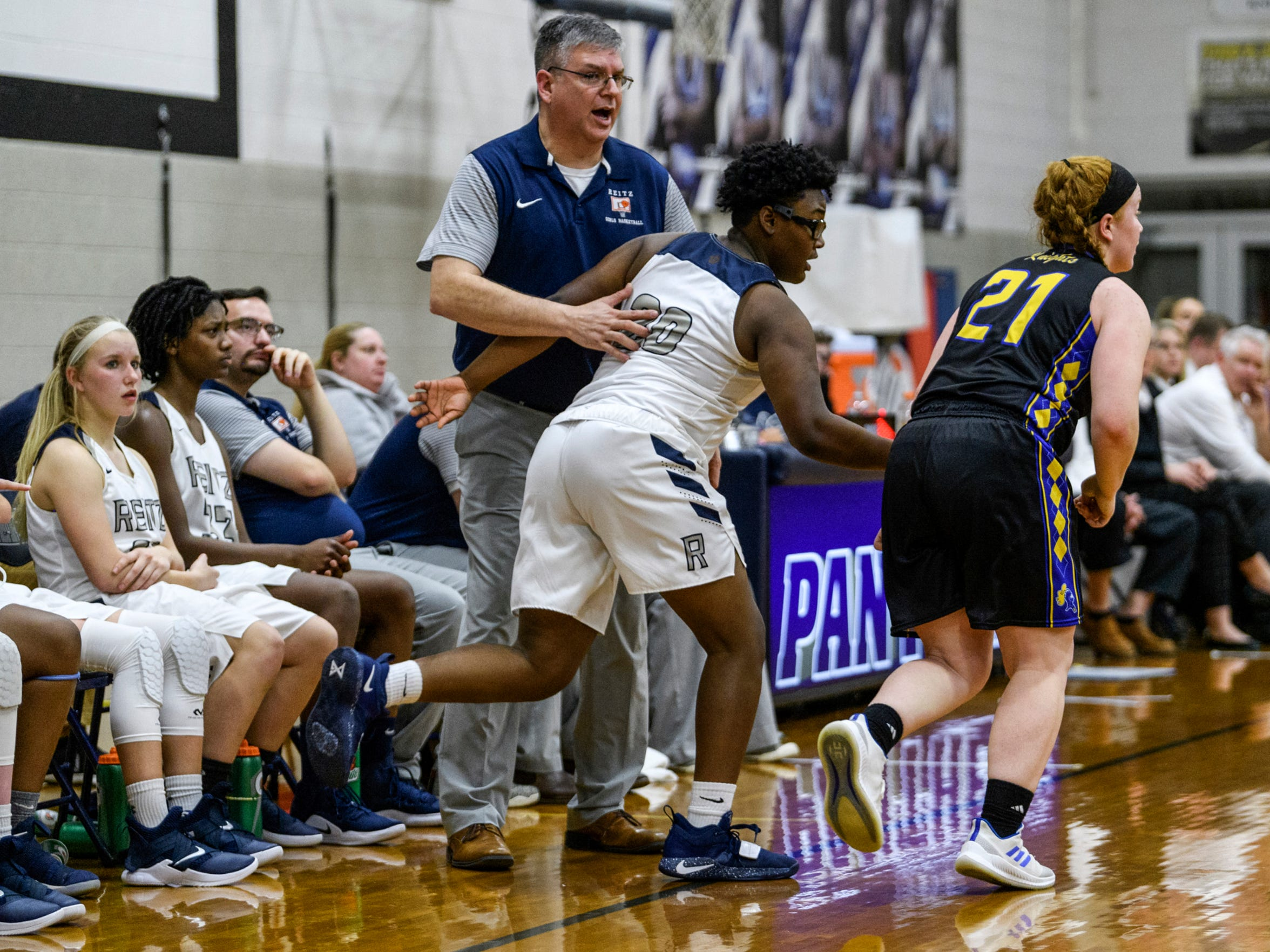 Reitz Head Coach Gary Loveless guides Reitz's Kyla Terry (30) back onto the court as their team takes on the Castle Knights at F.J. Reitz High School in Evansville, Ind., Thursday, Jan. 3, 2019. The Panthers were defeated by the Knights, 51-17.