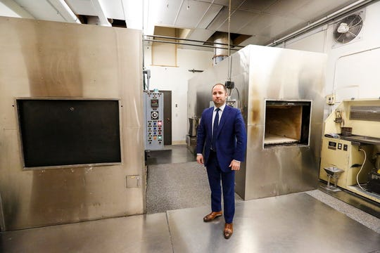 Jason Dill of Uecker-Witt Funeral Home in Fond du Lac stands next to two cremation ovens at Parkview Cremations. The crematorium handles about 1,000 cremations a year. Friday, December 21, 2018. Doug Raflik/USA TODAY NETWORK-Wisconsin