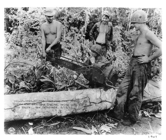 United States soldiers use a Mercury chainsaw during World War II.