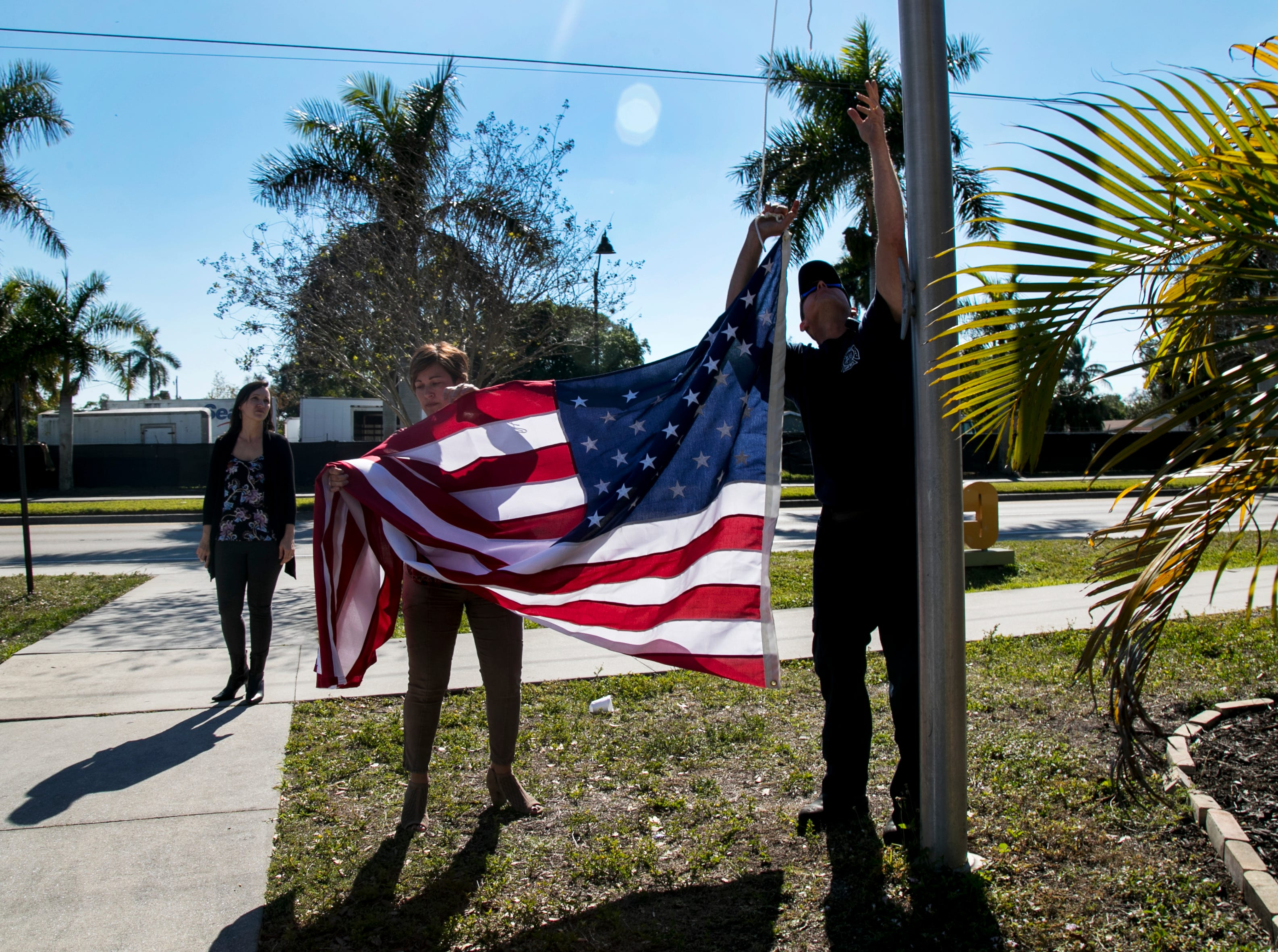 """Community Cooperative CEO Tracey Galloway, center, and Fort Myers firefighter Sean Shipman hang the new American flag at Community Cooperative on Tuesday afternoon in Fort Myers. They discovered their old flag was stolen - rope and all - on December 31, 2018, when they went to raise it back to full mast after the mourning period for former President George H.W. Bush. Galloway asked for help in hanging the new flag, and the Fort Myers Fire Department answered her call for help. They brought a ladder truck to replace the rope and hang the new flag. """"We work with a lot of veterans, so it's important for us to have a flag. We're glad to have it back up,"""" Galloway said."""