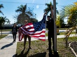 Fort Myers firefighters installed a new rope and flag at Community Cooperative in Fort Myers on Tuesday after their flag was stolen in December.