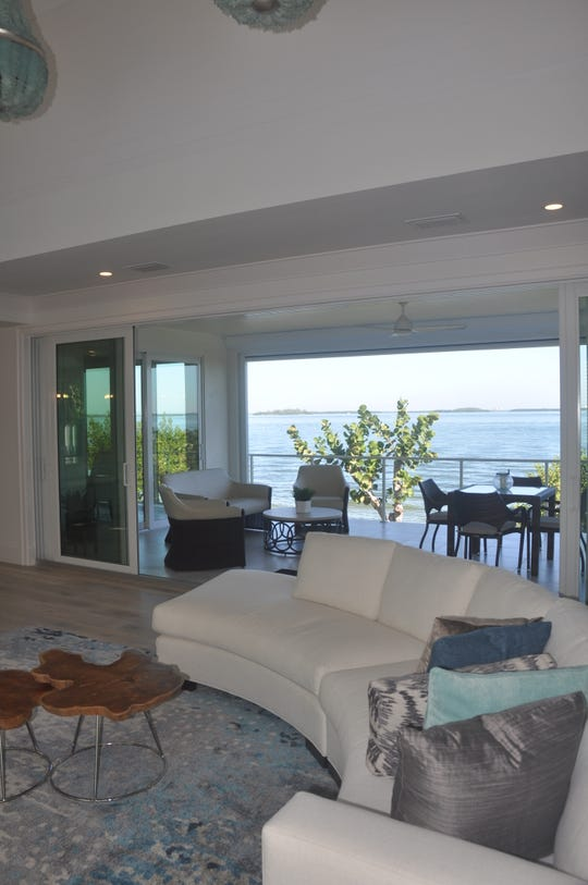 Sliding glass doors lead to a deck overlooking the pool and bay.