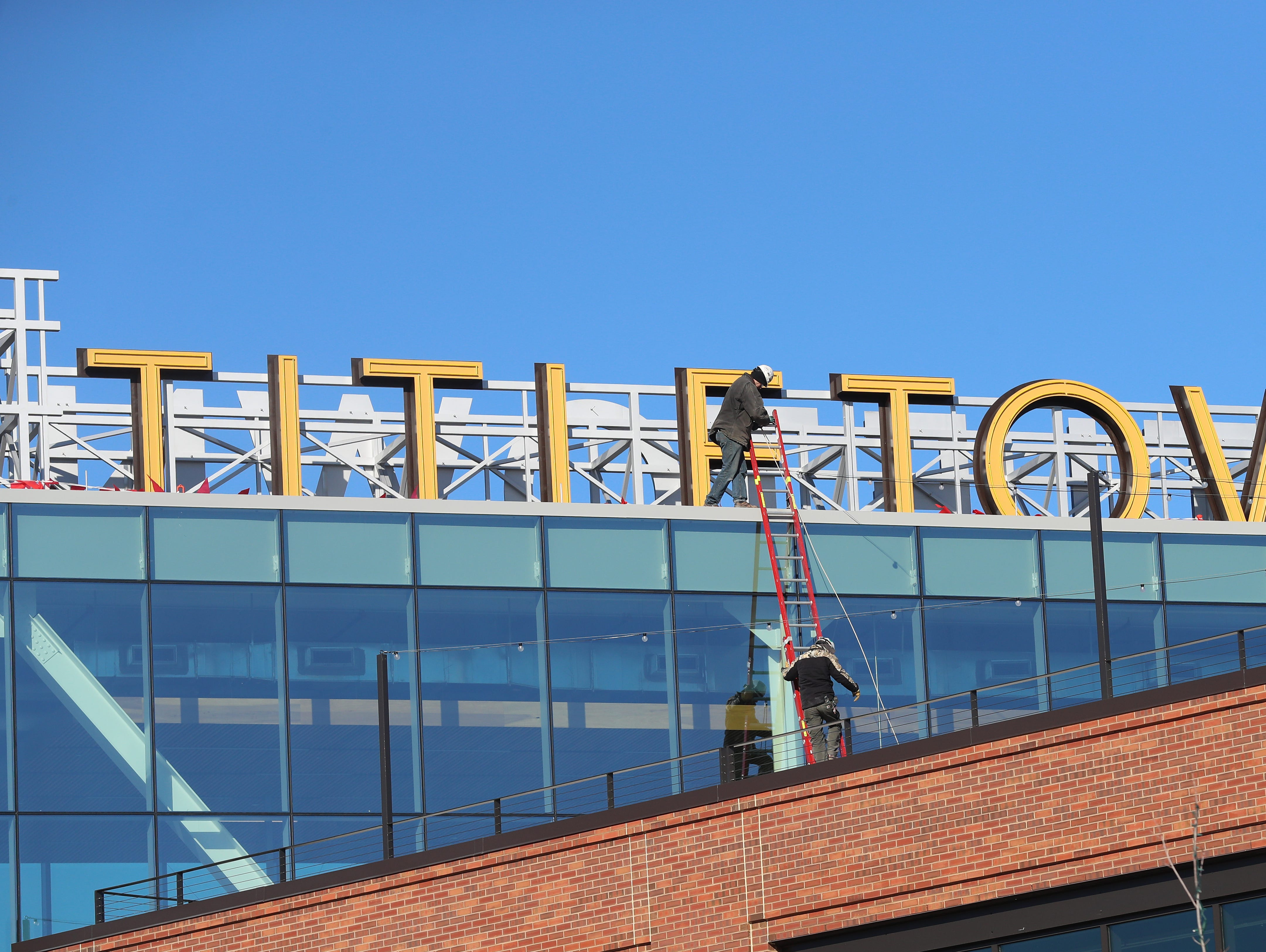 Workers install a new on the roof of the Titletown Technology building in the Green Bay Packers' Titletown District in Ashwaubenon.