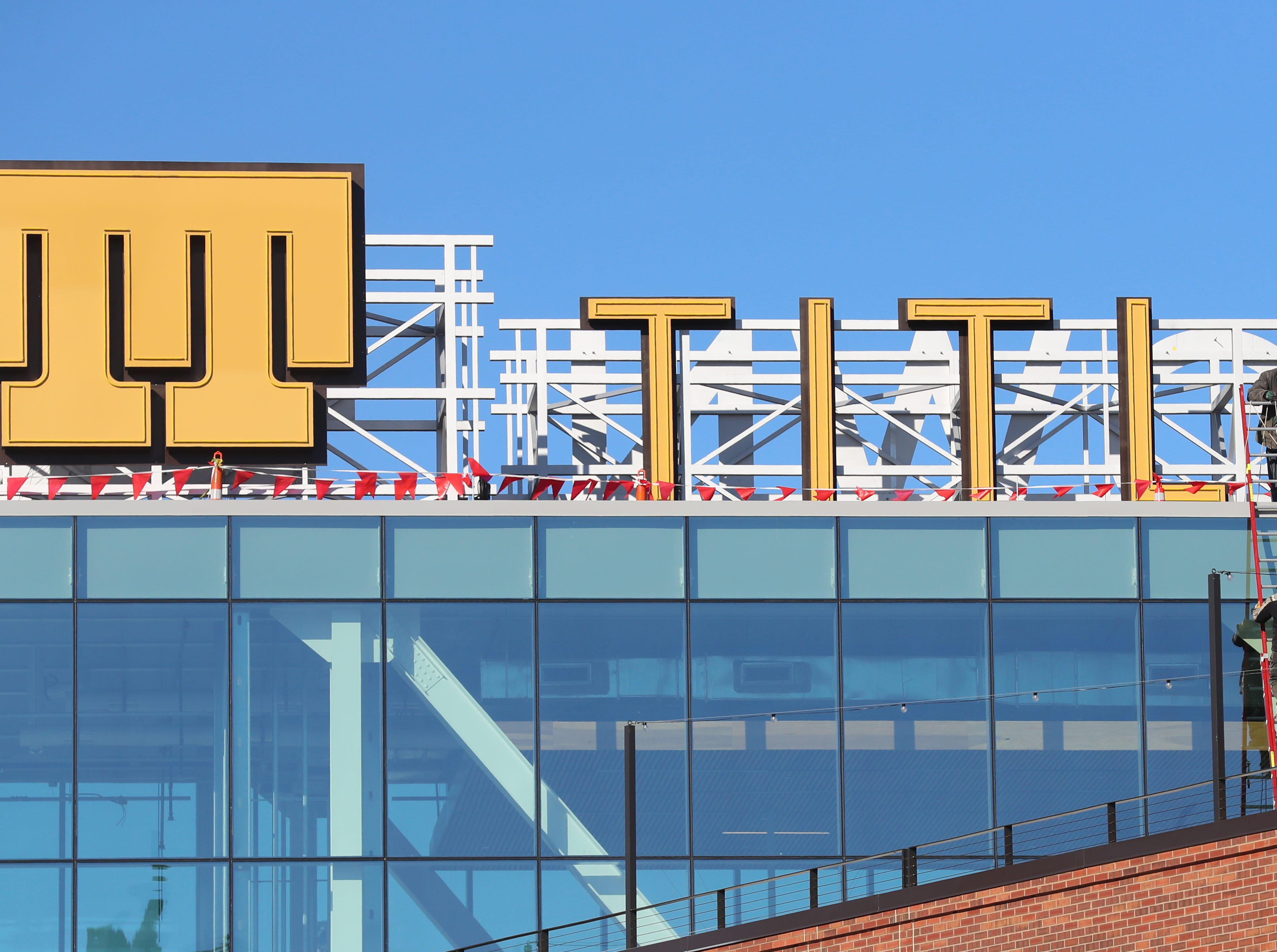 Workers install signage on the roof of the Titletown Technology building in the Titletown District Wednesday, January 16, 2019 in Green Bay, Wis.