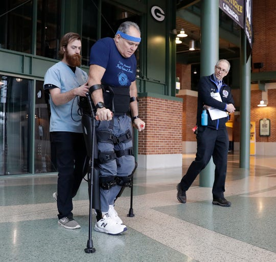 Zach Hodgson walks with Dean Juntunen as he maneuvers a robotic exoskeleton on Jan. 15 in the Lambeau Field Atrium. Joe Berman, Milwaukee Veterans Administration project manager, looks on.