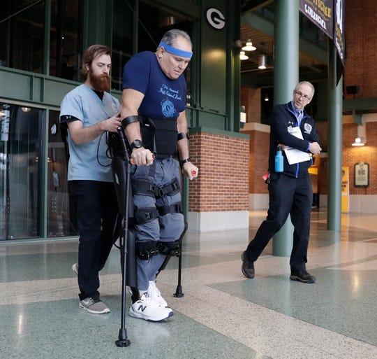 Zach Hodgson walks with Dean Juntunen as he maneuvers a robotic exoskeleton on Jan. 15 in the Lambeau Field Atrium. Joe Berman, Milwaukee Veterans Administration project manager, looks on.