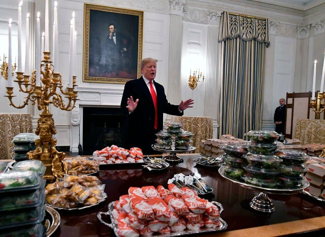 President Donald Trump looks over tables of fast food for the the college football playoff champion Clemson Tigers in the State Dining Room of the White House.