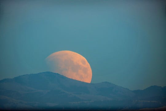 John Thomas of Great Falls took this photo of the moon as it rose over the Highwood Mountains during a lunar eclipse on Sept. 27, 2015. Another lunar eclipse will be visible from Great Falls Sunday evening.