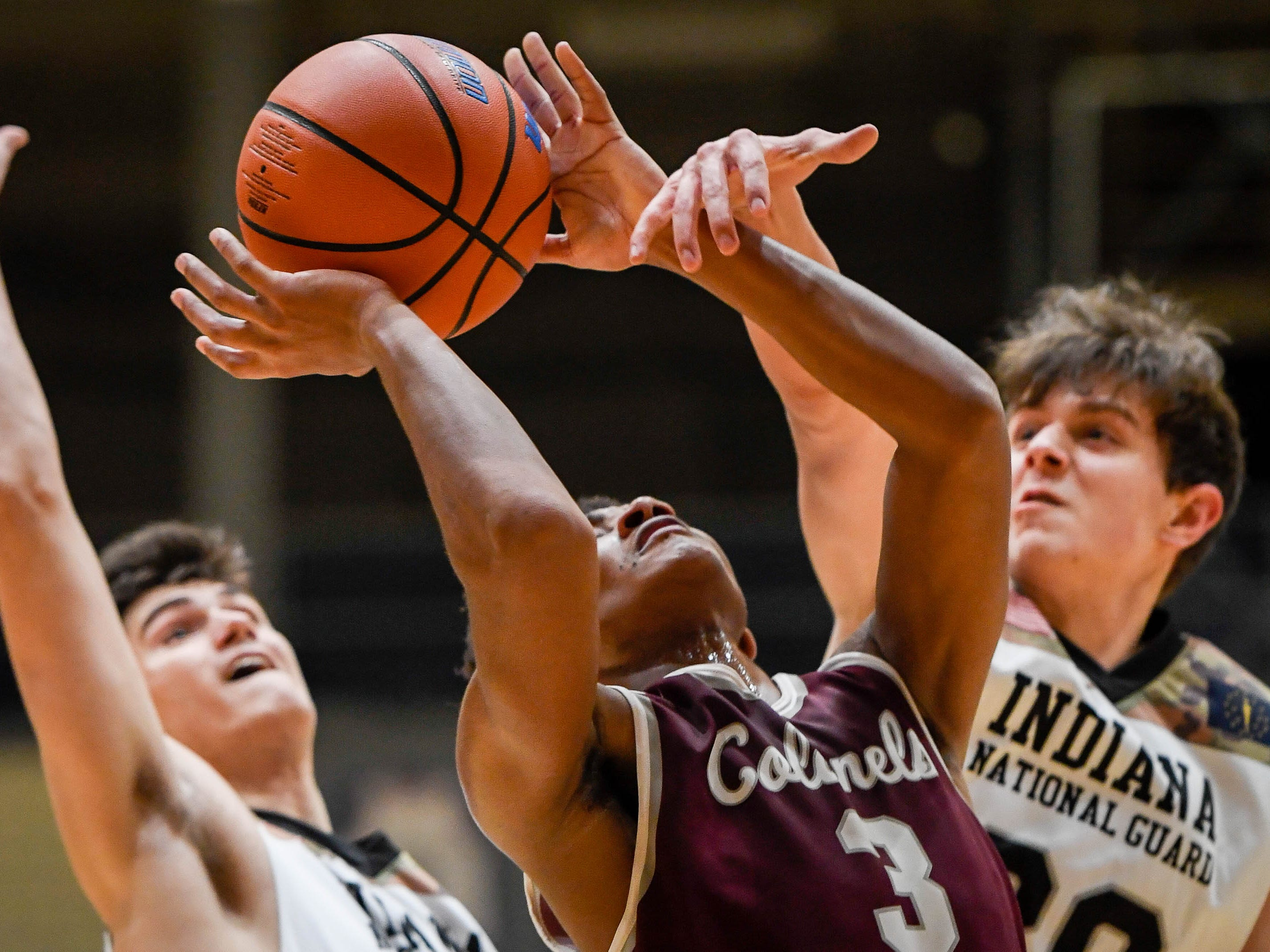 Henderson's Daymian Dixon (3) looks to shoot past defense from Castle's Louis Brock (34), left, and Castle's Bob Nunge (20) as the Castle Knights play the Henderson County Colonels in Paradise Tuesday, January 15, 2019.