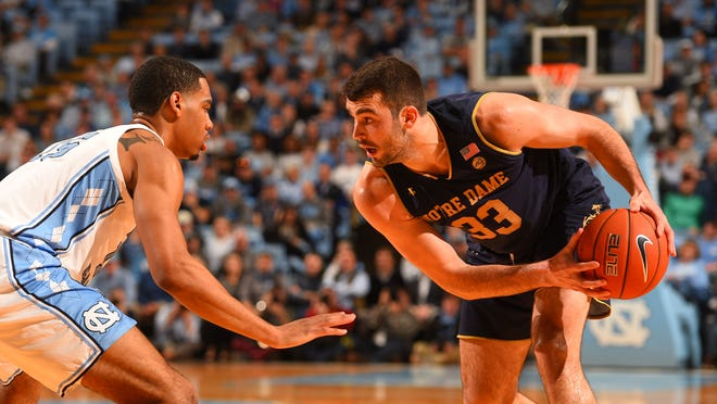 Jan 15, 2019; Chapel Hill, NC, USA; Notre Dame Fighting Irish forward John Mooney (33) with the ball as North Carolina Tar Heels forward Garrison Brooks (15) defends in the first half at Dean E. Smith Center.