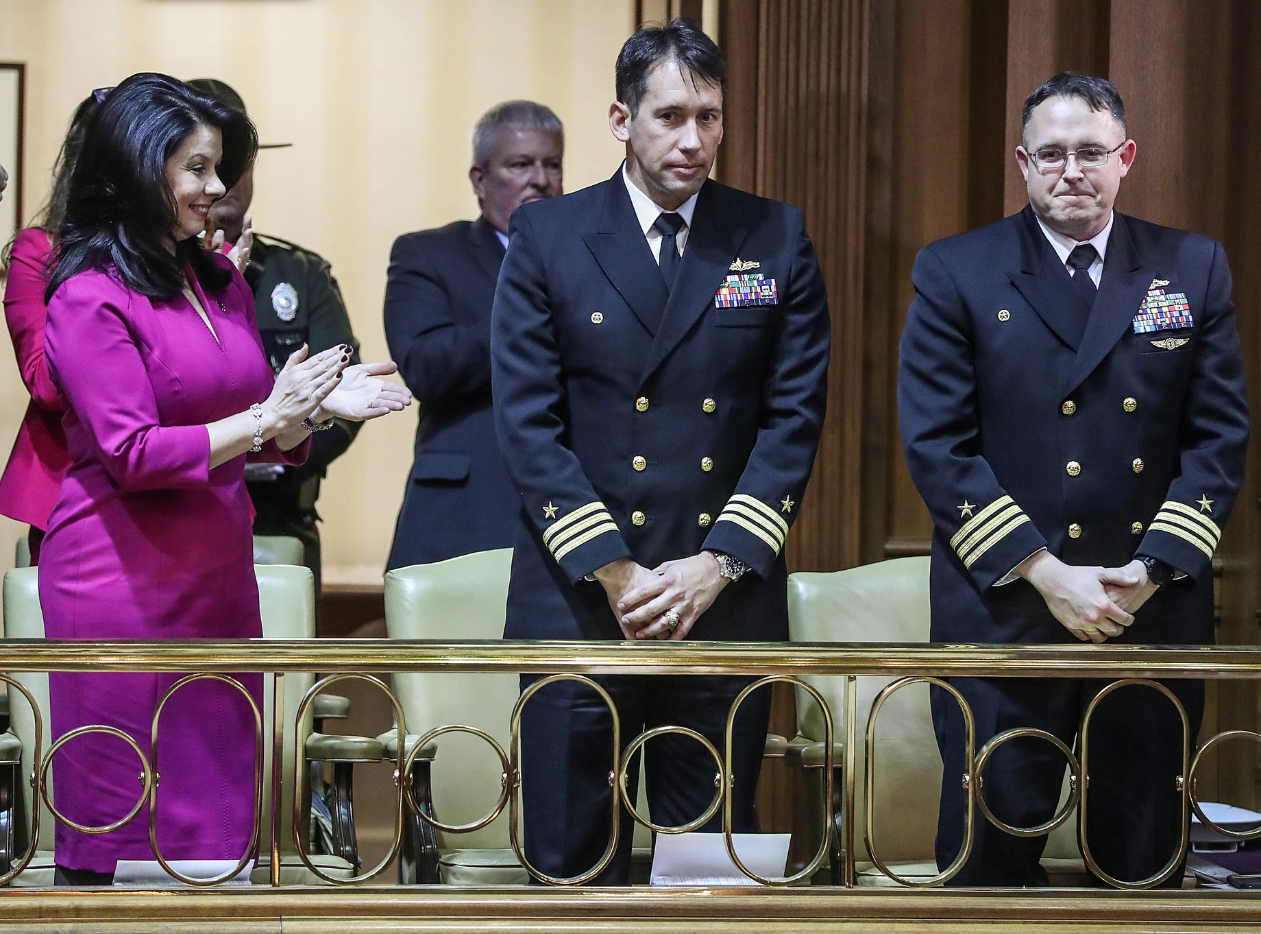 From left, Janet Holcomb stands with the Indiana General Assembly to honor Lt. Cmdr. Colin Kane and Cmdr. Dave Grogan, during the annual State of the State address at the Indiana Statehouse in Indianapolis, Tuesday, Jan. 15, 2019.