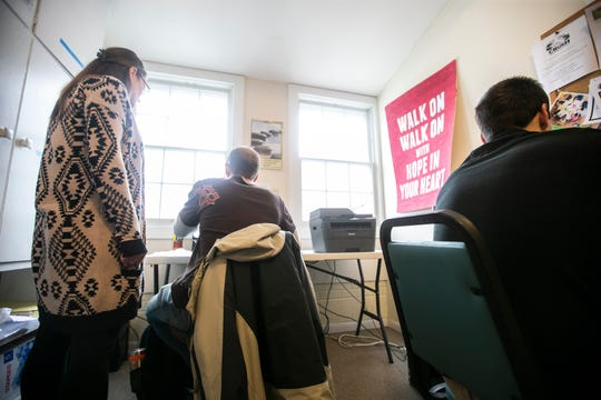 Michelle Heinz, Inside Out Reentry Community executive director, meets with community members as they work on job applications on Wednesday, Jan. 16, 2019, at the Inside Out Reentry Community building in Iowa City, Iowa.