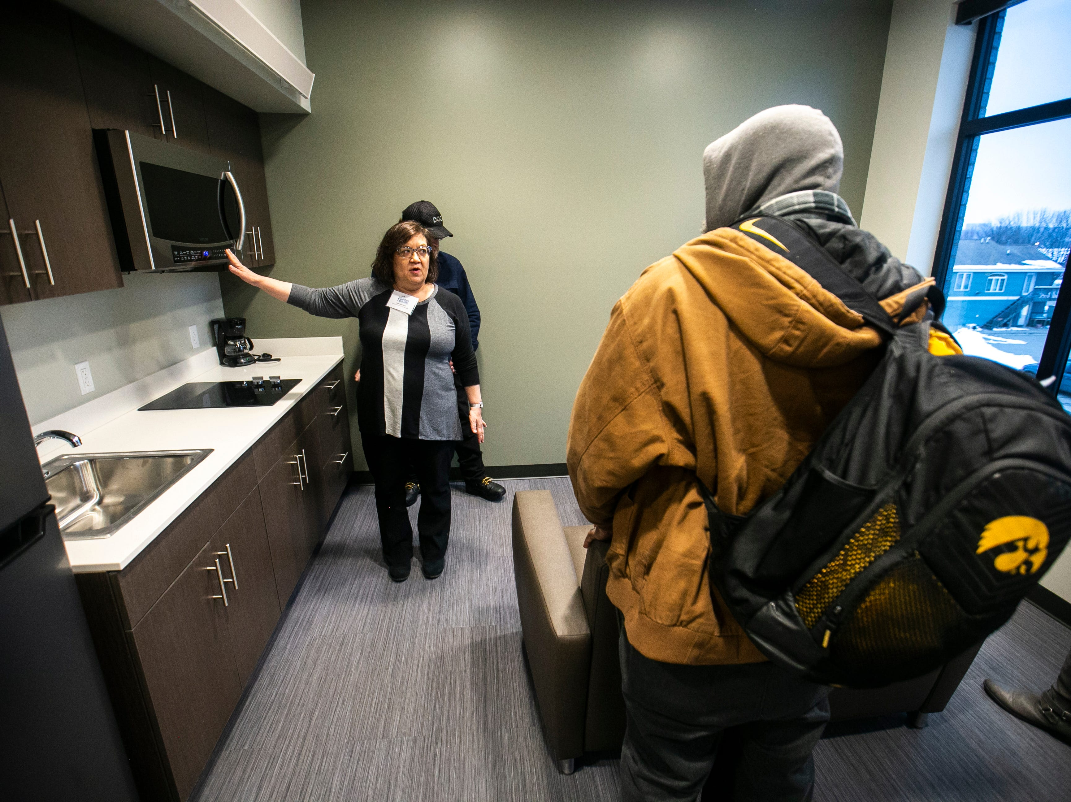 Community members tour the newly completed homeless housing apartment complex on Wednesday, Jan. 16, 2019, at Cross Park Place in Iowa City, Iowa.