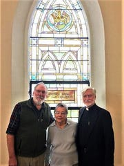 From left, Scott Sutcliffe, Mary Jamison and the Rev. Dr. Jeff Losey in front of a window in need of restoration at  Trumansburg United Methodist Church. The window was given by the children of Esther Farr, a member of the church for 26 years, who died in 1911.