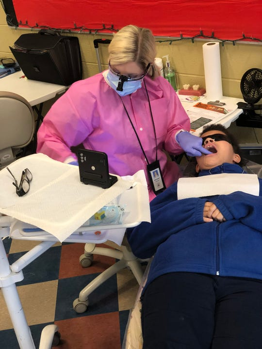 Kristin Bodiford, a registered dental hygienist with the Jackson-Madison County Regional Health Department, screens Ava Campbell, a sixth grade at West Bemis Middle School, Tuesday morning. Spending an average of three weeks at each school, Bodiford and other dental hygienists screen and apply sealants to approximately 2,400 students in JMCSS school each school year through a federally funded program.