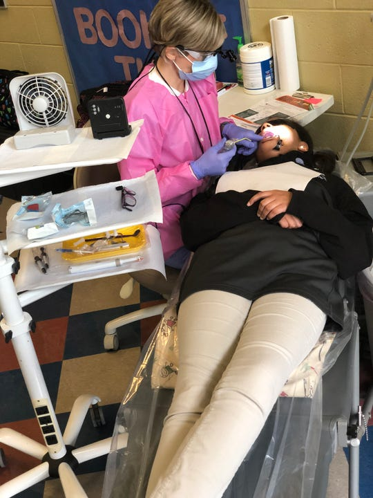 Chris Orwig, a registered dental hygienist with the Jackson-Madison County Regional Health Department, screens Maleah Cox, a sixth grade at West Bemis Middle School, Tuesday morning. Spending an average of three weeks at each school, Orwig and other dental hygienists screen and apply sealants to approximately 2,400 students in JMCSS school each school year through a federally funded program.