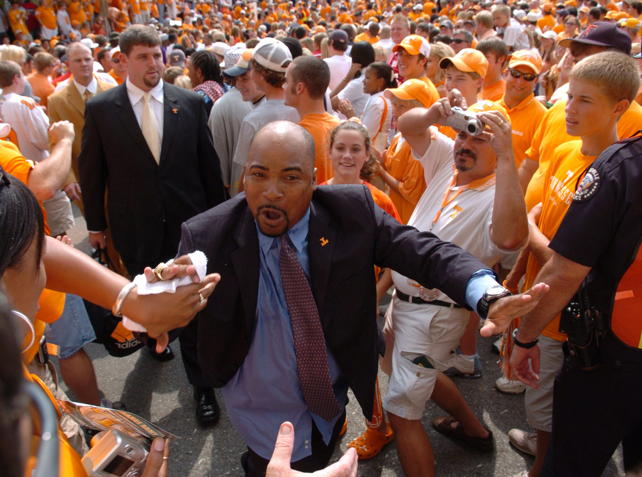 0902utcal.JA#6271.jpg -- sports --  UT receivers coach Trooper Taylor gets pumped up as he high fives fans during the Vol Walk outside of Neyland Stadium Saturday  prior to the Tennessee game against California. Jeff Adkins/NEWS SENTINEL ----09/02/2006.