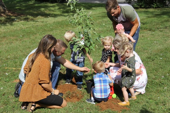 Zach and Whitney Bates and Chad and Erin (Bates) Paine plant a tree in memory of the children they have lost because of miscarriages.